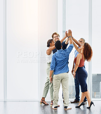 Buy stock photo Shot of a group of confident young work colleagues forming a huddle with their hands at work during the day