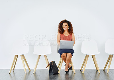Buy stock photo Shot of a confident young woman working on her laptop while being seated in a waiting room during the day