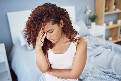 Buy stock photo Shot of an attractive young woman suffering from a headache in her bedroom