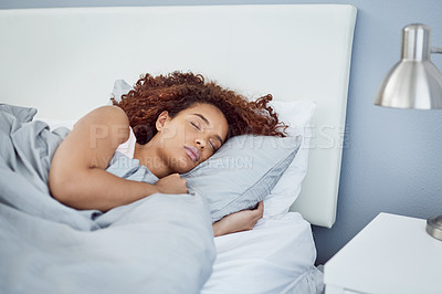 Buy stock photo Shot of an attractive young woman fast asleep in her bed at home