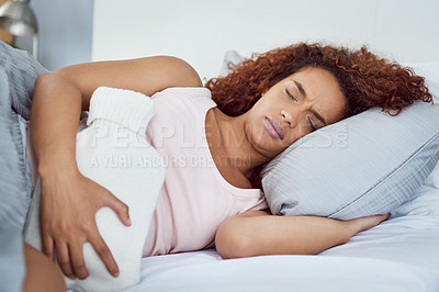 Buy stock photo Shot of an attractive young woman suffering from stomach cramps in her bedroom