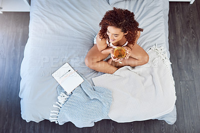 Buy stock photo High angle shot of a woman drinking tea and writing in her diary while sitting on her bed at home