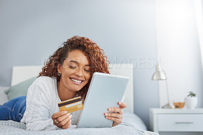 Buy stock photo Shot of a young woman using a digital tablet and credit card in her bedroom at home