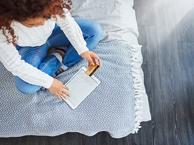 Buy stock photo High angle shot of a young woman using a digital tablet and credit card in her bedroom at home