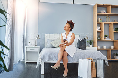 Buy stock photo Shot of a young woman using a cellphone while relaxing in her bedroom with shopping bags around her
