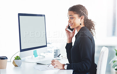 Buy stock photo Shot of a young businesswoman talking on a cellphone while working in an office