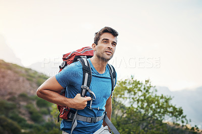 Buy stock photo Cropped shot of a carefree young man looking into the  distance while going for a hike up a mountain