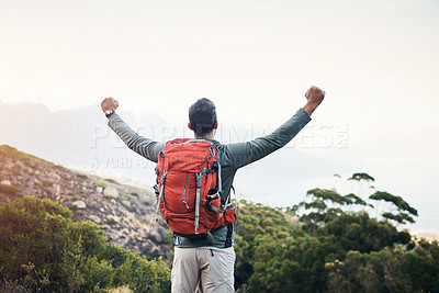 Buy stock photo Cropped shot of a cheerful young man lifting his arms in the air  and looking into the distance while going for a hike up a mountain