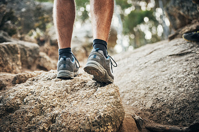 Buy stock photo Low angle shot of an unrecognizable man walking on rocks up a mountain outside during the day