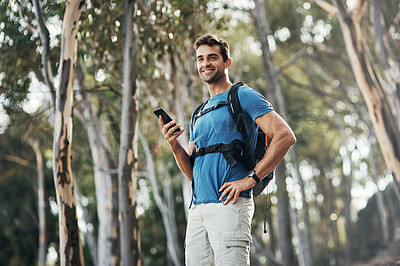 Buy stock photo Cropped shot of a cheerful young man texting on his cellphone while going for a hike up a mountain