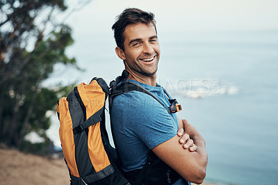 Buy stock photo Portrait of a cheerful young man standing with his arms folded while going for a hike up a mountain