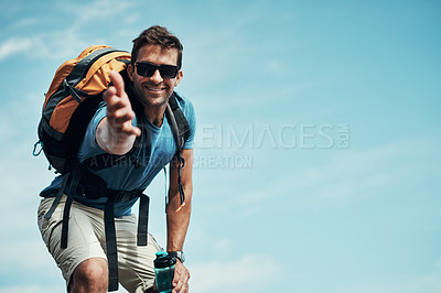 Buy stock photo Portrait of a cheerful young man stretching out his hand to help while going for a hike up a mountain