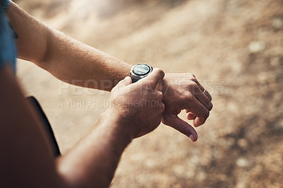 Buy stock photo Cropped shot of an unrecognizable man configuring his wristwatch while going for a hike up a mountain