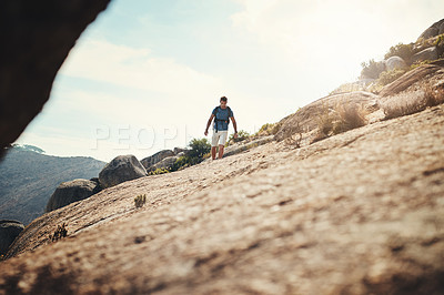 Buy stock photo Cropped shot of a carefree young man going for a hike up a mountain outside during the day