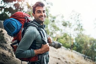 Buy stock photo Portrait of a carefree young man going for a hike up a mountain outside during the day