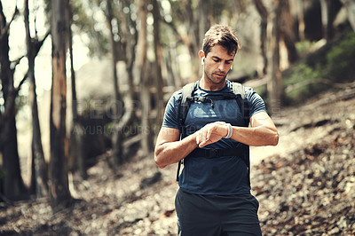 Buy stock photo Cropped shot of a handsome young man checking his watch while out hiking in the mountains