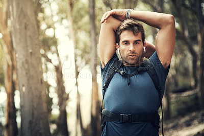 Buy stock photo Cropped portrait of a handsome young man stretching before heading off on his hike in the mountains