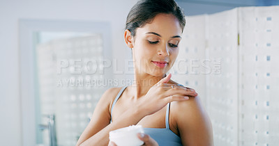 Buy stock photo Cropped shot of a cheerful young woman looking at her reflexion in the mirror and applying moisturizer to her skin in the morning