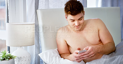 Buy stock photo Cropped shot of a handsome young man using his smartphone while still in bed at home