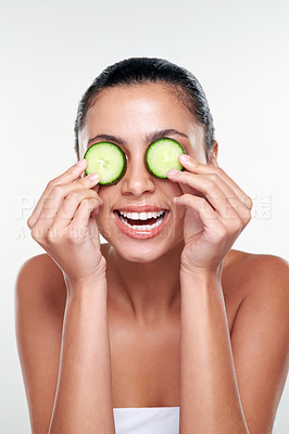 Buy stock photo Shot of a beautiful young woman covering her eyes with cucumbers against a studio background