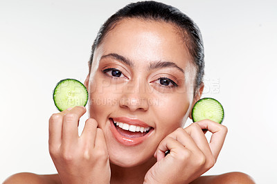 Buy stock photo Shot of a beautiful young woman holding cucumber slices against a studio background