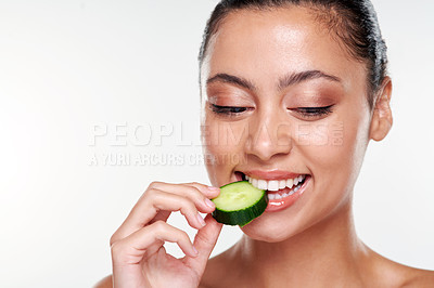 Buy stock photo Shot of a beautiful young woman eating a cucumber slice against a studio background