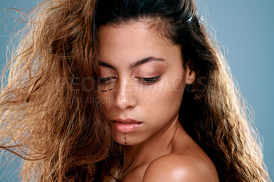 Buy stock photo Shot of a beautiful young woman with cosmetic surgery markings on her face against a grey studio background
