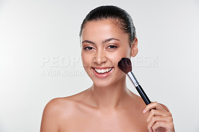 Buy stock photo Shot of a beautiful young woman applying makeup with a brush against a studio background