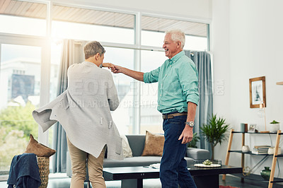 Buy stock photo Shot of a beautiful senior couple dancing together in their home