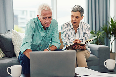 Buy stock photo Shot of a senior couple using a laptop together while relaxing in their lounge at home