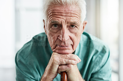 Buy stock photo Portrait of a senior man sitting down and leaning on his walking stick at home