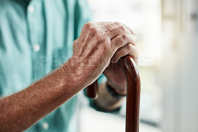 Buy stock photo Shot of an unrecognizable senior man holding his walking stick at home