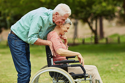 Buy stock photo Shot of a cheerful senior man pushing his wheelchair bound wife around the park