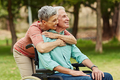 Buy stock photo Shot of a cheerful senior woman hugging her wheelchair bound husband in the park