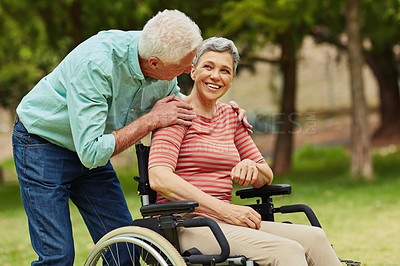 Buy stock photo Shot of a cheerful wheelchair bound senior woman relaxing with her husband in the park