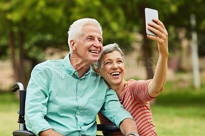 Buy stock photo Shot of a cheerful senior woman taking a selfie with her wheelchair bound husband in the park