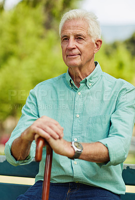 Buy stock photo Shot of a cheerful senior man siting on bench and holding his walking stick in the park