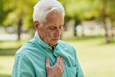 Buy stock photo Shot of a senior man suffering from chest pains while spending the day at the park