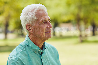 Buy stock photo Shot of a senior man looking thoughtful while relaxing in the park