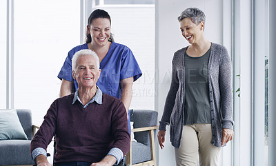 Buy stock photo Shot of a senior man in a wheelchair supported by his wife and nurse at a retirement home