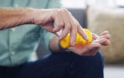 Buy stock photo Shot of an unrecognisable senior man taking medication at home