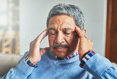 Buy stock photo Shot of a senior man suffering from a headache at home