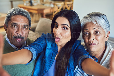 Buy stock photo Shot of a cheerful senior couple and their daughter taking a selfie together while sitting on a couch at home