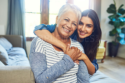 Buy stock photo Portrait of a beautiful senior woman posing with her daughter while relaxing on a sofa at home
