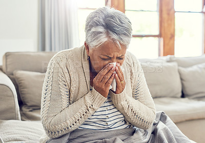 Buy stock photo Shot of a sickly senior woman blowing her nose with a tissue while sitting on a sofa ta home