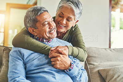 Buy stock photo Shot of an affectionate senior couple relaxing on a sofa together at home