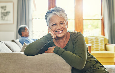 Buy stock photo Portrait of a beautiful senior woman relaxing on a couch with her husband in the background