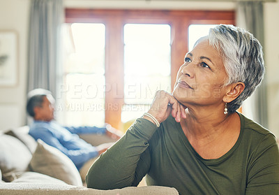 Buy stock photo Shot of a beautiful senior woman sitting on a couch and  looking very thoughtful with her husband in the background