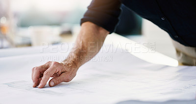 Buy stock photo Shot of an unrecognizable architect working on a blueprint in his office