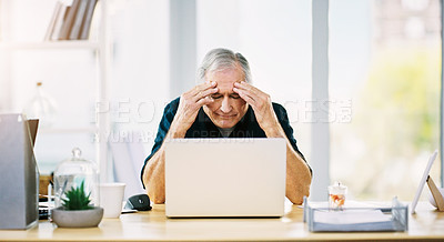 Buy stock photo Shot of a mature businessman suffering from a headache in his office